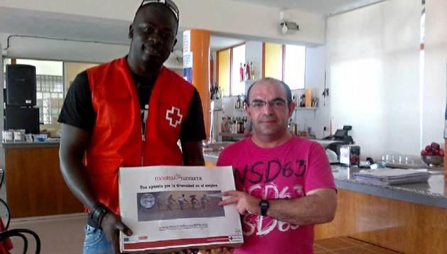 Entrega de los manteles en Tudela de la mano del voluntario y mediador intercultural de Cruz Roja Tudela, Allasane Ndiaye.