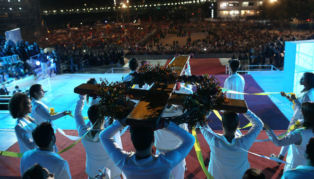 Voluntarios cargan una cruz en la vigilia dirigida por el papa Francisco