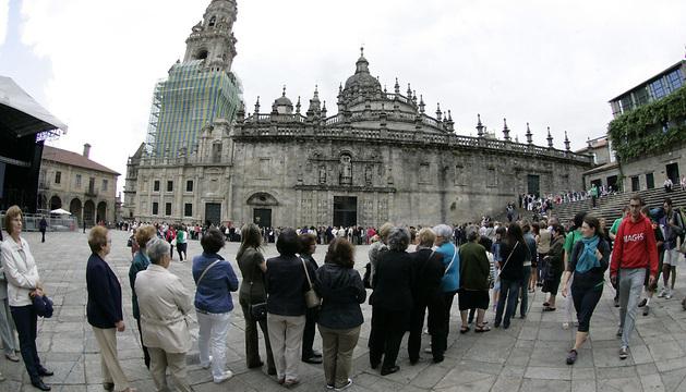 Decenas de personas hacen cola en la entrada de la catedral de Santiago de Compostela.