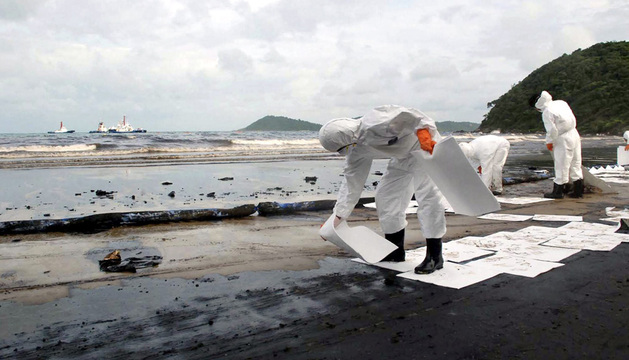 Operarios utilizan papel absorbente para retirar el crudo de las playas de la isla de Samet.