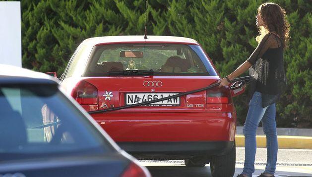 Una mujer reposta combustible en una gasolinera.