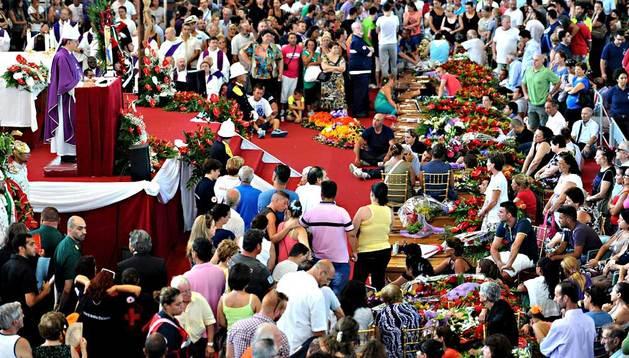 Una multitud asiste al funeral de las víctimas mortales del accidente de autocar, en el que fallecieron 38 personas, celebrado en el palacio de deportes de la localidad de Pozzuoli (Italia) este martes.