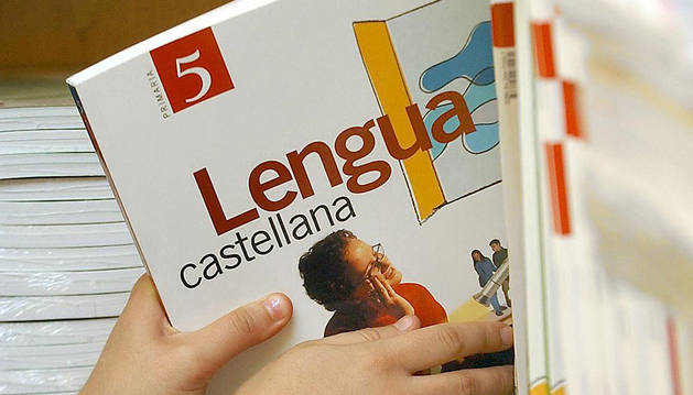 Una profesora coge un libro de 5º de Primaria de una estantería.