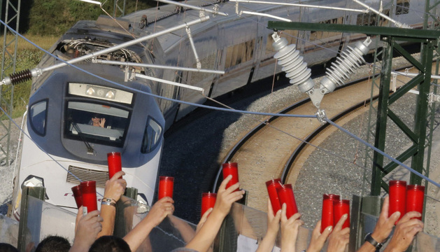 Los vecinos de Angrois alzan los cirios este miércoles, mientras el conductor los saluda, al paso tren que hace la ruta del que descarriló al cumplirse una semana del accidente.