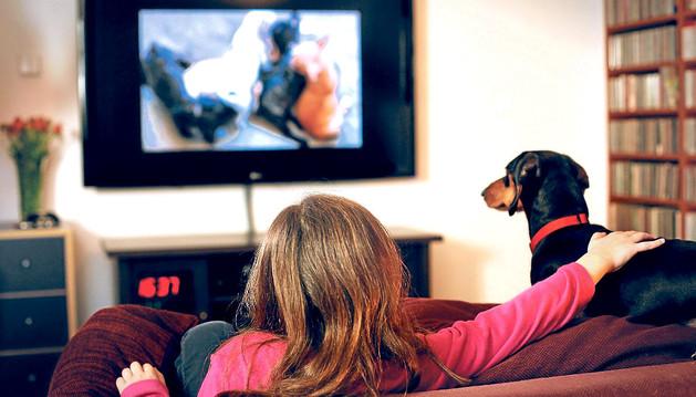 Un perro y su dueña contemplan la emisión del nuevo canal de televisión DogTV.