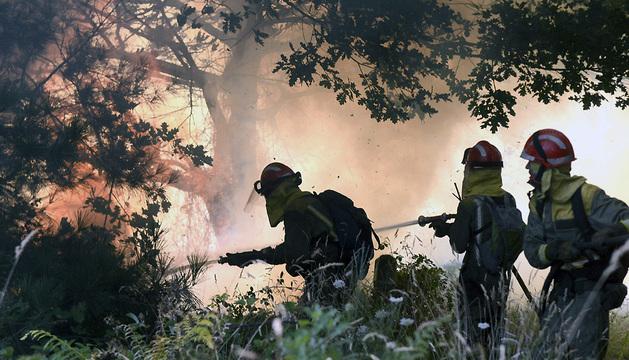 Varios brigadistas se enfrentan a las llamas cerca del pueblo de Loureiro, en Ourense.