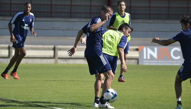Puñal disputa el balón junto a Ariel Núñez ante la presencia de Arribas. Al fondo, Lotiés y Armenteros, que ha completado todo el entrenamiento de Osasuna en Tajonar