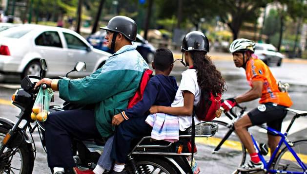 Fotografía del 3 de agosto de 2013 de un motorizado transportando dos niños por una calle de Caracas (Venezuela).