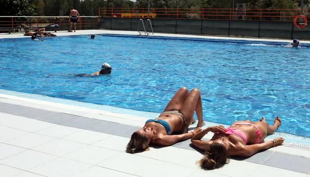 Dos chicas toman el sol en una piscina.