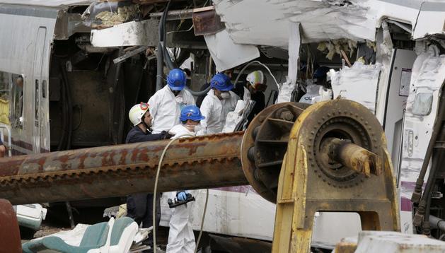Agentes de la policía científica investigan y recogen datos en los vagones accidentados del tren Alvia.