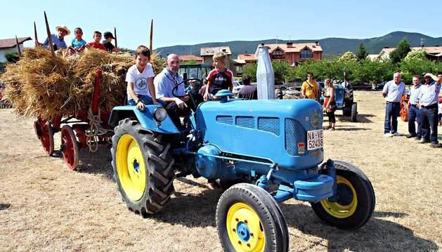 Un grupo de niños disfrutan de una vuelta en un tractor de los años 50 en el Día de la Trilla de 2012.