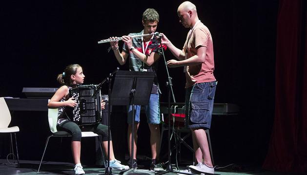 Dos alumnos con el director del área de música, el compositor Isaac Miguel, el martes por la tarde durante el show, abierto al público