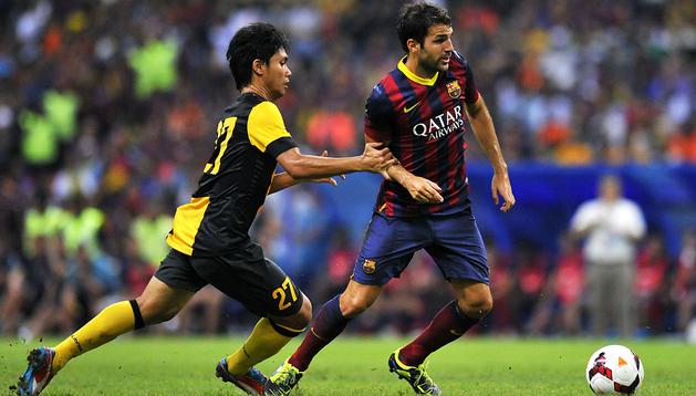 Cesc Fábregas conduce el balón en presencia de un rival del Malasya XI