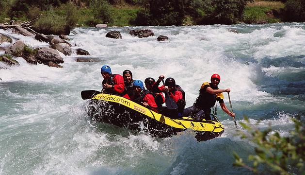 Un grupo de personas hace rafting.