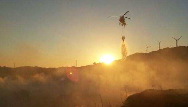 Un helicóptero echa agua para apagar el incendio.