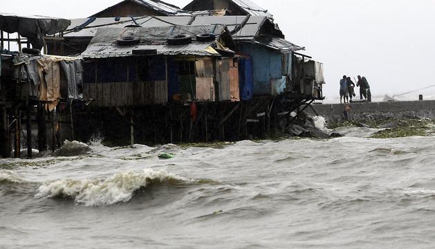 Pescadores caminan junto a la costa en Manila (Filipinas).