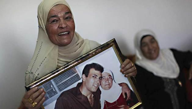 Naamih Mansour (i), de 60 años de la localidad cisjordana de Dier Jarer, cerca de Ramalla, muestra una fotografía de su hijo Esmat Mansour que ha permanecido en una cárcel israelí 21 años y que será excarcelado de acuerdo con el plan Israel.