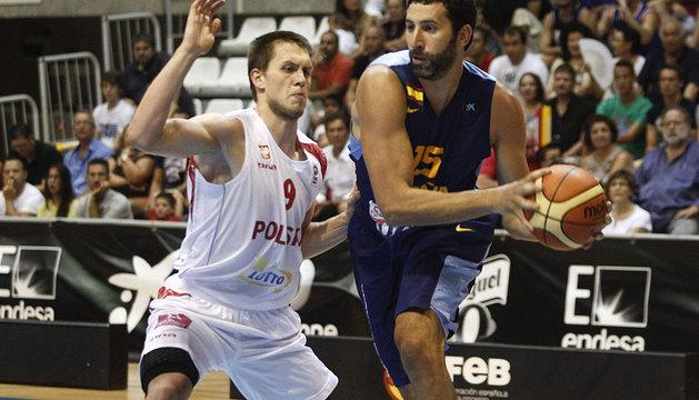 El jugador de la selección española Alex Mumbrú (d) es defendido por Mateu Ponitka, de Polonia.