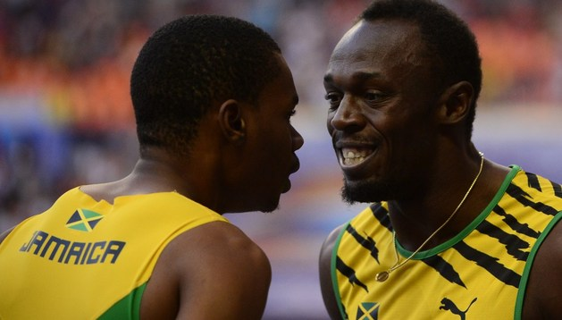 Usain Bolt celebra su triunfo junto a su compatriota Warren Weir, segundo en la carrera