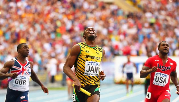 Usain Bolt (centro) sonría tras superar en primer lugar la meta en los 4x100 relevos