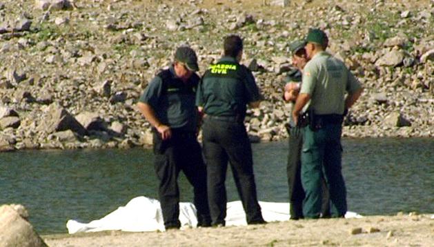 Miembros del equipo de rescate custodian los cuerpos.