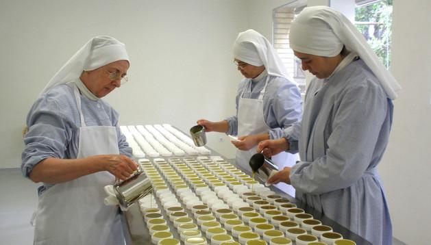 Tres religiosas rellenan los tarros con la crema que vierten de unas jarras de acero inoxidable.
