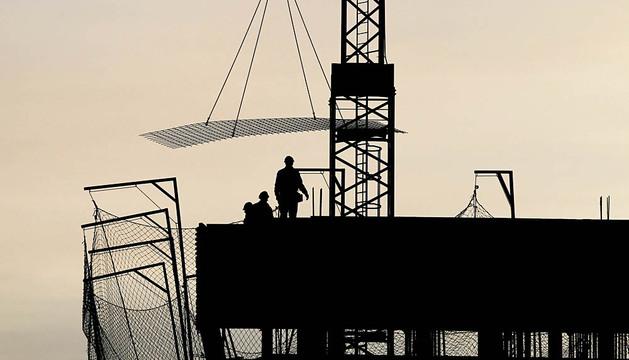 Tres operarios trabajan en plena puesta de sol en lo alto de un bloque de viviendas en construcción en el nuevo desarrollo  de Lezkairu