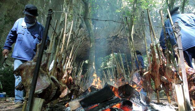 Las piezas de cordero ensartadas en varas de avellano, asándose al fuego, junto a la cueva de Zugarramurdi.