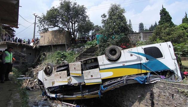 Un policía de Indonesia junto al autobús accidentado