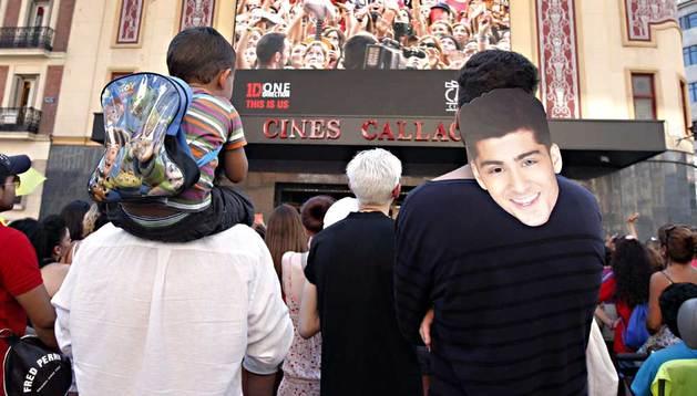 Un seguidor del grupo One Direction, ataviado con una máscara de la cara del cantante Zayn Malik, de los muchos que acudieron este martes a la plaza de Callao como una