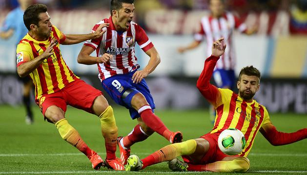 David Villa busca el disparo entre Piqué y Jordi Alba