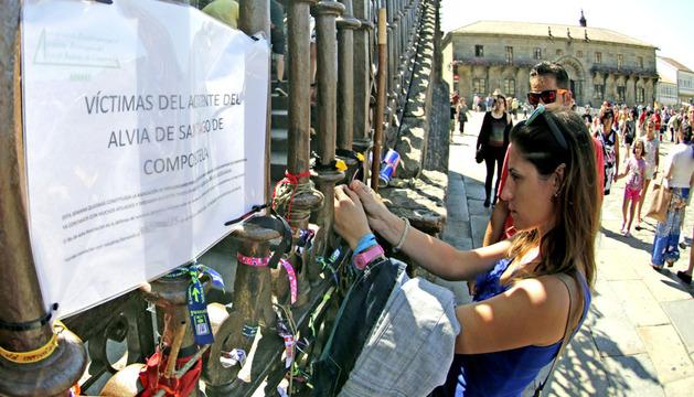 Una joven coloca su pulsera en el altar improvisado en la fachada de la catedral de Santiago en memoria de las víctimas del accidente del tren Alvia