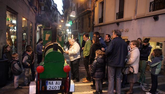 Varias personas hacen cola ante el castañero de la calle Comedias