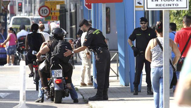 Un guardia civil palpa la mochila de una motorista en la frontera gibraltareña.