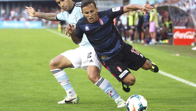 El cefensa del Granada Hugo Mallo (dcha.) lucha un balón con el centrocampista argentino del Granada Diego Buonanotte