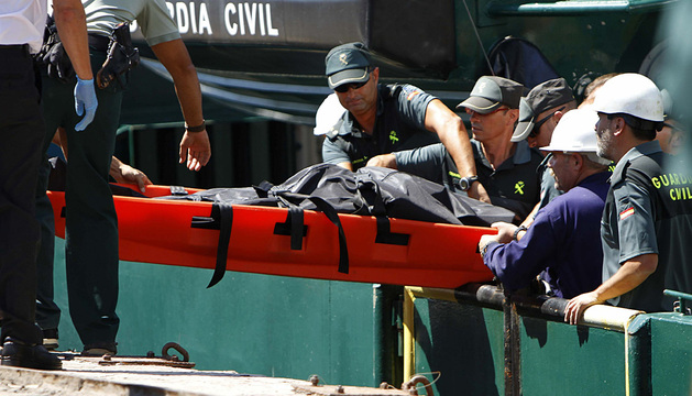 Agentes de la Guardia Civil trasladan a tierra el cadáver del tripulante desaparecido.