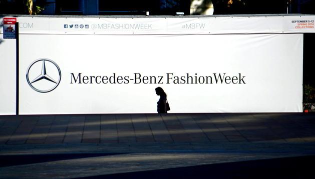 Una mujer camina frente al cartel que anuncia la Semana de la Moda