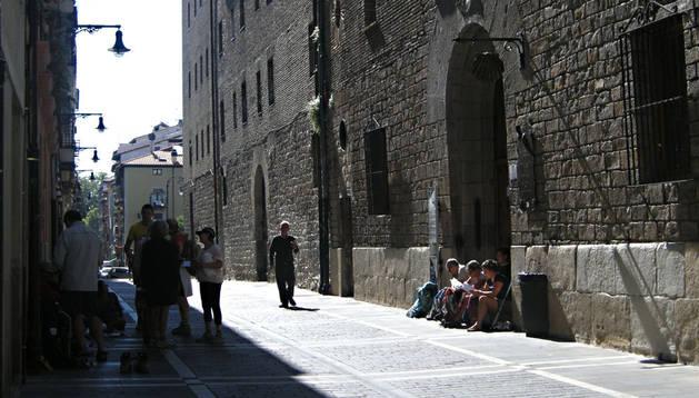 Varios peregrinos esperando delante de la puerta del albergue Jesús y María de Pamplona.