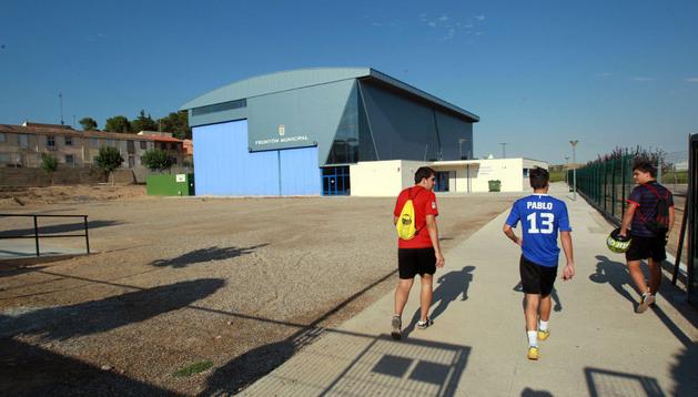Tres jóvenes caminan junto al solar donde se construirá el cuartel, junto al frontón municipal.