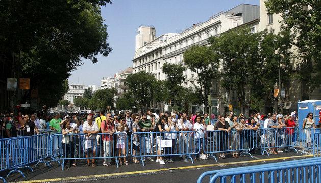 Varios personas contemplan los últimos preparativos en la Puerta de Alcalá
