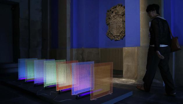 Una mujer observa algunas de las obras que forman parte de la exposición
