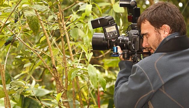 Un joven saca una fotografía con una cámara reflex.
