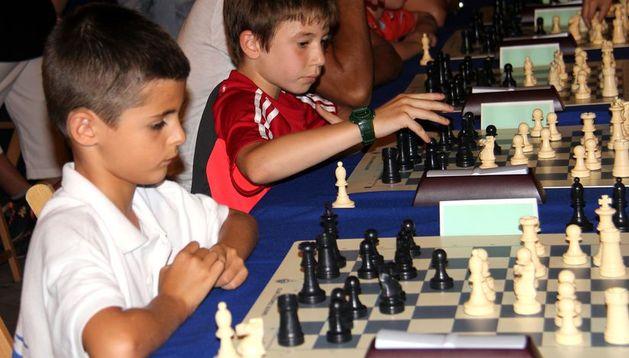 Dos niños participan en un campeonato de ajedrez.