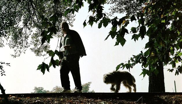 Un hombre pasea con su perro por el parque del Arga.