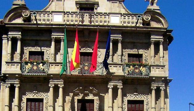 Un turista fotografía a un grupo de personas frente a la fachada del Ayuntamiento de Pamplona.
