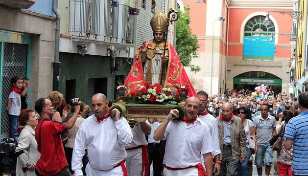 Imágenes de la procesión en honor a San Fermín de Aldapa, ondeo de la bandera de la ciudad y danza de espadas.