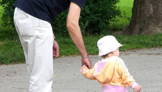Un padre pasea junto a su hija.