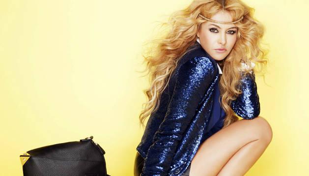 Paulina Rubio posando con un bolso de su colección.