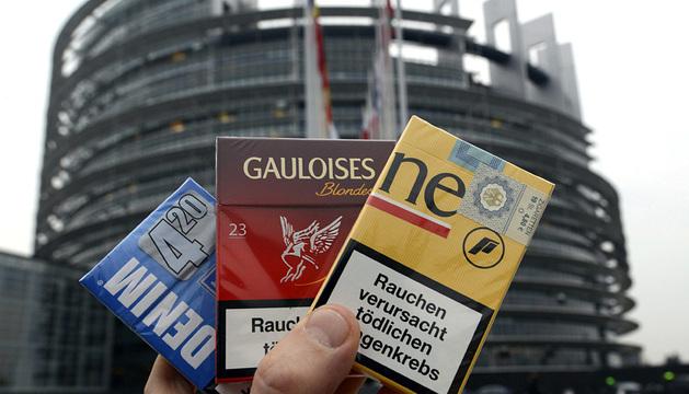 Una persona muestra tres paquetes de cigarrillos delante del Parlamento Europeo en Estrasburgo.