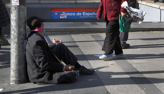 Un hombre mendiga en una calle del centro de Madrid.